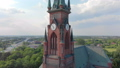 Church in small city among pastures. Drone footage. Red Church is Roman Catholic church. 49064238