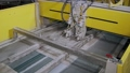industrial cutting machine is slicing ceramic tiles, moving over transporting tape 49076346