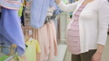 pregnancy concept - pregnant woman choosing blue baby bodysuit at clothing store 49138802