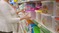Pregnant woman is choosing plastic storage container in supermarket store 49138803