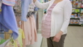 pregnant woman choosing baby bodysuit at clothing store 49138806