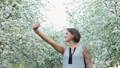 Young cute tattooed woman is taking selfie on cellphone in blooming apple orchard 49187091