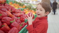 little boy in supermarket smelling red bulgarian peppers. Shopping in store, fresh products for 49204884