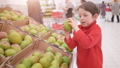 Funny little boy picking mango from the box, during family shopping in hypermarket 49204885