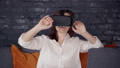 Adult woman is sitting on sofa and using new digital technology of augmented 3d reality simulation. 49214578