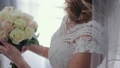 Young girl in a wedding dress is holding a bouquet of the bride. Close-up. Wedding bouquet 49261146