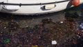 garbage, trash and other rubbish pollution floating in water next to boat 49262631