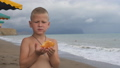 Child on the beach eating cheese bread. 49290935