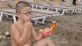 Child on the beach eating cheese bread. 49290938