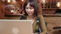 Pretty young female blogger working in a cafe environment 49335337