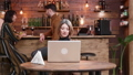 Woman being served coffee while working on her laptop in a vintage style cafe 49335345