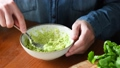 Person mashing avocado in bowl on wooden table 49396740