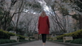 Backview of attractive blonde girl in a red coat walking the sakura alley, enjoying the scent of 49410684