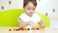Portrait of a happy child. A little boy sits at the table and takes bright fruit candies, marmalade 49420704