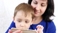 Portrait of a woman and child. Happy family: Mom and son hold a smartphone and play with the 49420707