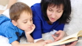 Portrait of a happy family. Mother reads a book to her child. Close-up. 49420710