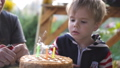 Little boy three years old blowing candles on birthday cake. Closeup slow motion. 3840x2160 49448390