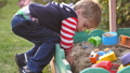 Little toddler boy playing in sandbox on playground in sunny day 49448394