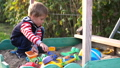Little toddler boy playing in sandbox on playground in sunny day 49448424