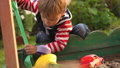 Little toddler boy playing in sandbox on playground in sunny day 49448425