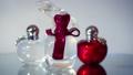 Modern glass perfume bottles rotate on white backg 49488767