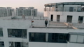 Aerial shot of beautiful european girl standing on the edge of roof top of modern apartments 49518825