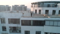 Aerial shot of beautiful european girl waving hands on the edge of roof top of modern apartments 49518897
