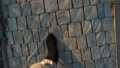 Top view of female legs in suede boots and pleated skirt walking on the sidewalk 49544463