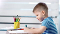 Concentrated little creator boy drawing beautiful colorful art picture using marker at album 49548740