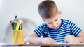 Medium close-up diligent concentrated little child boy drawing picture using blue marker 49548741