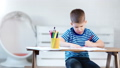 Pensive little kid boy concentrated writing on paper using colorful pencil at white modern interior 49548742