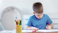 Enthusiastic little boy writing on paper using colorful pencil at classroom medium shot 49548749