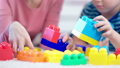Close-up hands of female child psychologist and little boy playing with colored cubes during testing 49548755