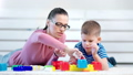 Medium close-up carefree young mother playing constructor cubes with little cute son 49548759