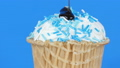 Chocolate sauce icing flows over ice cream in a waffle cup on blue background 49563587
