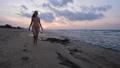 Woman in bikini walking on sea beach at sunset 49565422