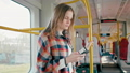Woman is Listening to Music from Smartphone with Earphones, Travelling by Train 49569197