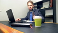 a man in a suit works at a desk in the office on a laptop and drinks coffee from a disposable cup 49583620