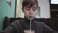 Teen boy sits in a cafe and drinks orange juice from a glass with a straw 49587992