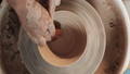 Potter making ceramic pot on the twisted pottery wheel. Top view. Potter at work, close up. Handmade 49594386