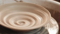 An empty plate with relief rotates on the pottery wheel, close up. Winding clay structure. Handmade 49594983