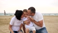 Happy mom and dad kiss their child on a sandy beach against the sea, smiling, in slow motion 49595809