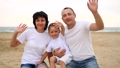 Happy family of three on the sea sandy beach, smiling and waving hand to the camera in slow motion 49595830