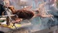 Whole pig skewered and grilled in open fire spining on a spit 49597379