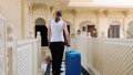 Woman checks into the hotel and rolls the suitcase to her room. 49631581