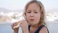 Little blonde girl is eating sandwich for breakfast sitting in terrace. 49631596