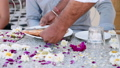 Waiter brings breakfast to a couple sitting at the table covered with flowers. 49631602