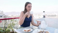 Woman is having a breakfast in cafe on terrace on city and mountain background. 49633876