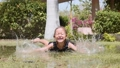 Happy little girl enjoy splashing laying in puddle on the lawn in park. 49633893