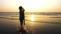 Little girl is running on the sea to waves holding surfboard in her hands. 49633896